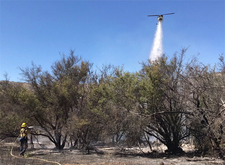 Firefighters attack a brush fire at the Rancho Oso Campground from the air and on the ground. (Photo courtesy Mike Eliason/Santa Barbara Co. Fire Dept.)