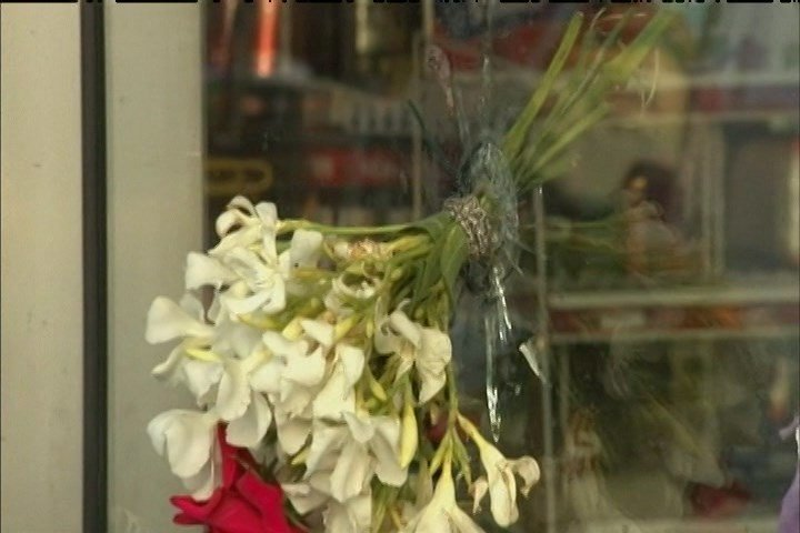 Flowers are placed through a bullet hole at an Isla Vista store following a deadly shooting in 2014. (KSBY photo)