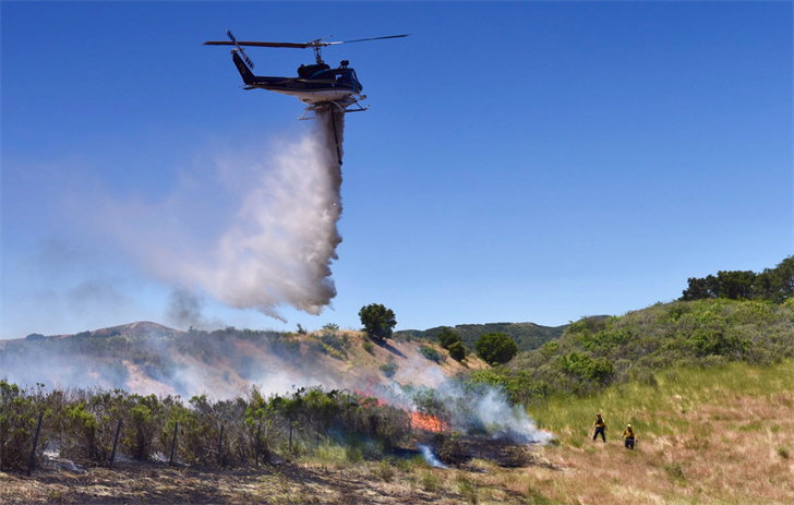 A helicopter drops water on a brush fire along Highway 1 south of Lompoc. (Photo courtesy Mike Eliason, Santa Barbara Co. Fire Dept.)