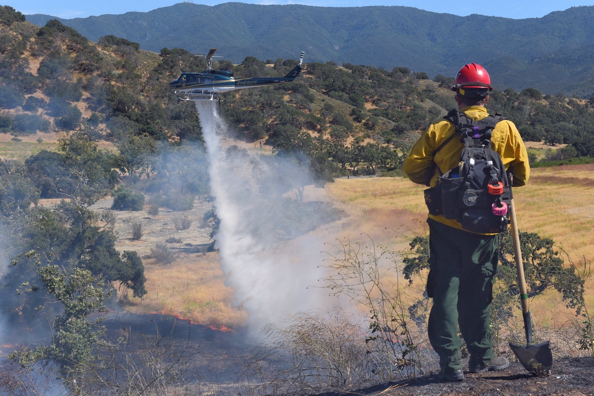 A helicopter drops water on a fire in the Santa Ynez Valley. (Photo courtesy Mike Eliason, Santa Barbara Co. Fire Dept.)