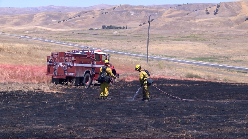 Firefighters extinguish a grass fire near Shandon. (KSBY photo)