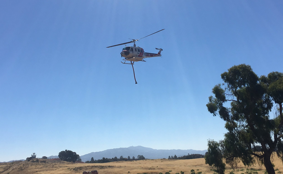 A helicopter makes drops at the Hill Fire on Tuesday. (KSBY photo)
