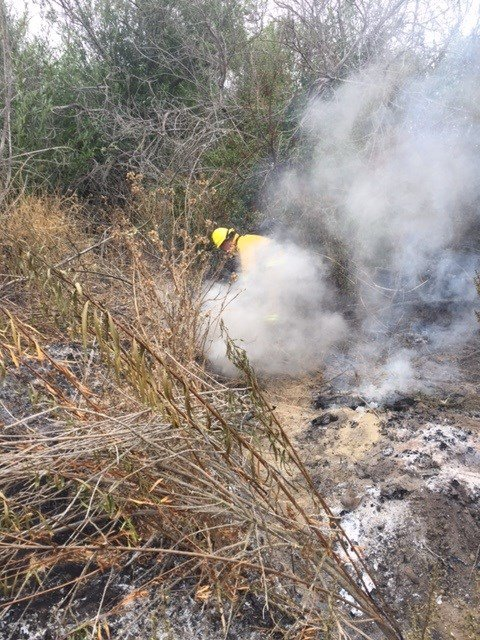 A firefighter works to extinguish a brush fire in the Santa Ynez River bed near Lompoc. (Photo courtesy Battalion Chief Brian Federmann)