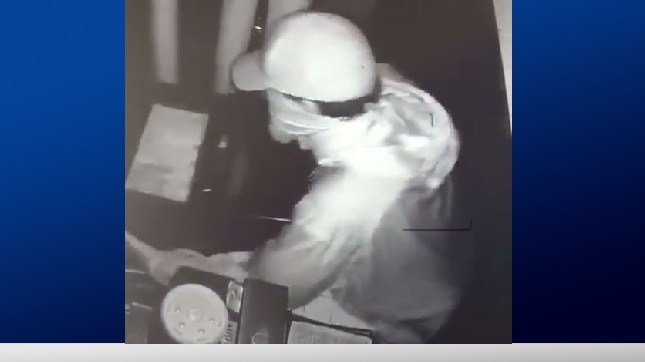 A surveillance image from Garcia's Mexican Restaurant shows a burglar stealing a cash register.