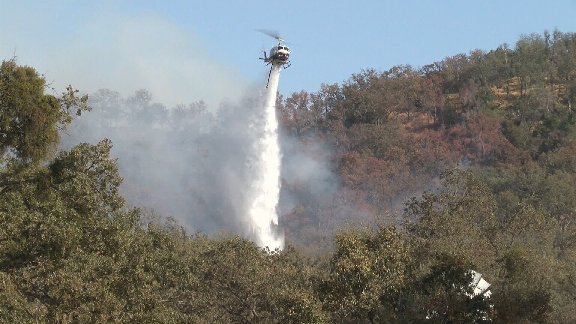 A helicopter drops water on the Pozo fire. (KSBY photo)