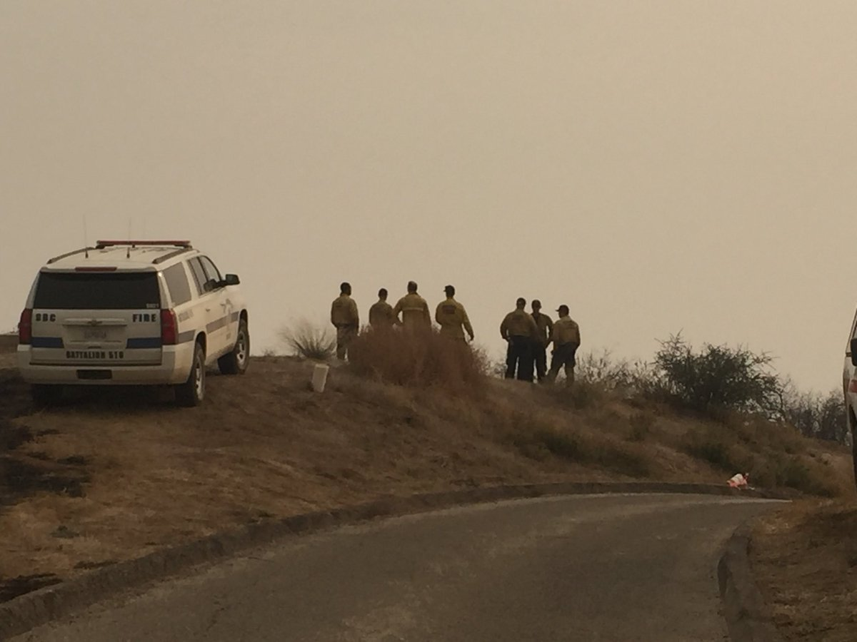 Fire crews watching the water drops through the smoke. The active fire is on the adjacent ridge in Carpinteria. (KSBY photo)
