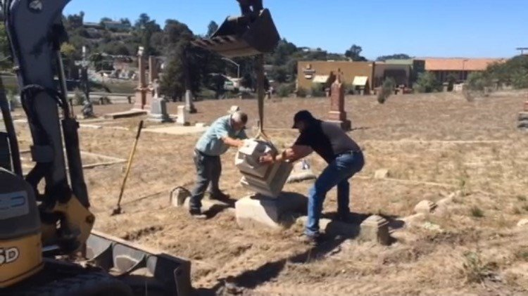 Workers restore a damaged headstone at St. Patrick's Cemetery in Arroyo Grande. (KSBY)